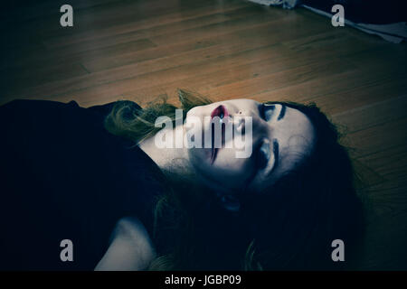 Dead girl on the floor with blood from her mouth and nose - Stock Photo
