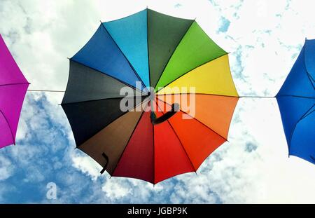 Rainbow color umbrella on the blue cloudy sky background in Gdynia, Poland - Stock Photo
