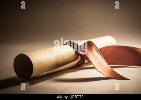 A parchment diploma scroll, rolled up with red ribbon laid at an oblique angle.  Processed to give a vintage or - Stock Photo