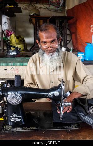 Male sewing machine operator, Pyin Oo Lwin, Myanmar - Stock Photo