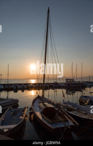 Boats in the harbour at sunset at Lazise, Lake Garda, Italy - Stock Photo