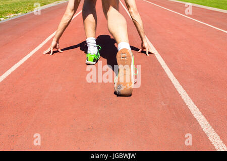 An exhausted athlete on a running track wearing broken green running shoes with big holes in the sole. - Stock Photo