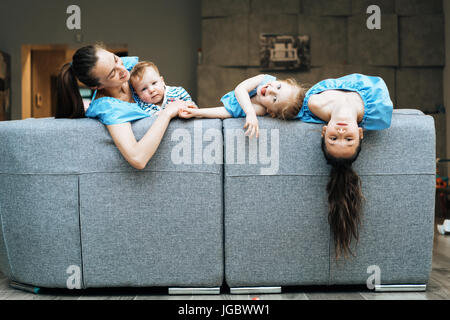 Mom, two daughters and a little son on the couch - Stock Photo