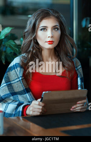 Girl wrapped in a blanket sits with tablet in hands. - Stock Photo