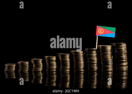 Eritrean flag with lot of coins isolated on black background - Stock Photo
