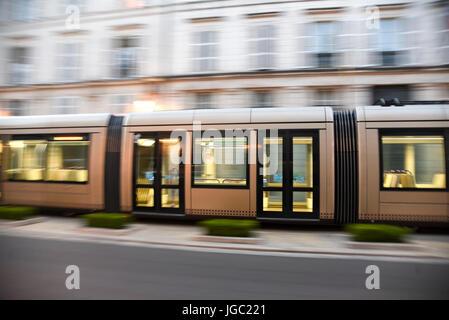 Speeding brown tram on Rue Jeanne d'Arc in Orleans, France - Stock Photo