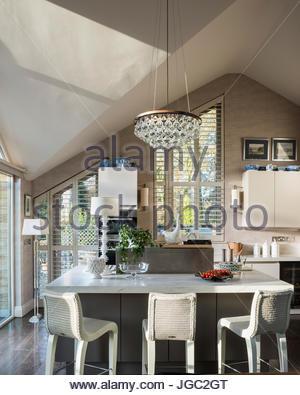 Lightbulb pendant above breakfast bar in A-frame kitchen - Stock Photo
