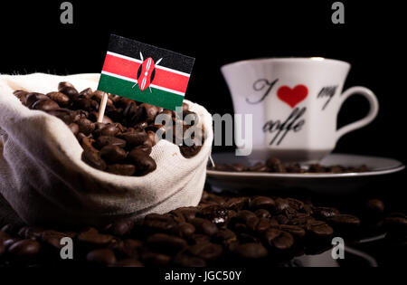 Kenyan flag in a bag with coffee beans isolated on black background - Stock Photo