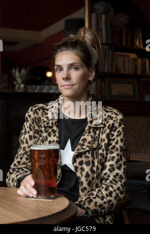 A modern young woman drinking real ale in a London pub - Stock Photo