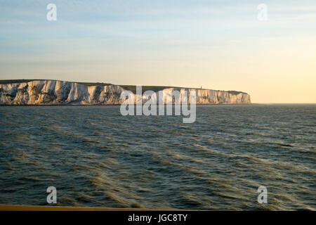 An early morning cross channel ferry passes the white cliffs of Dover, Kent, UK heading for Calais, France. - Stock Photo