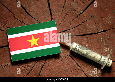 Suriname flag on a stump with syringe injecting money in flag - Stock Photo