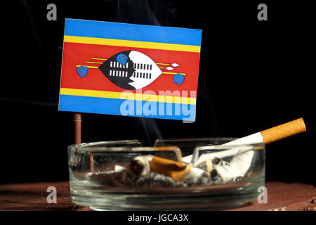 Swaziland flag with burning cigarette in ashtray isolated on black background - Stock Photo