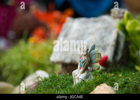 Magical miniature garden with a little fairy sitting in lush green moss alongside a small hut in a mystical village - Stock Photo