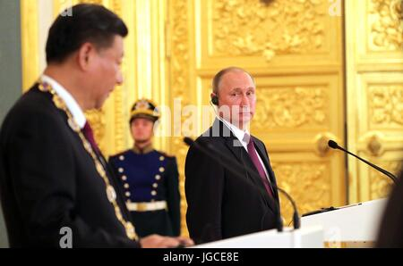 Russian President Vladimir Putin listens to Chinese President Xi Jinping after awarding him the Order of St Andrew - Stock Photo