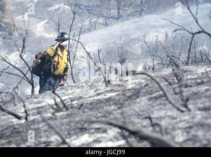 San Clemente/Talega, California, USA. 5th July, 2017. An OCFA Wild Lands Fire Fighter mops up hot spots using a - Stock Photo