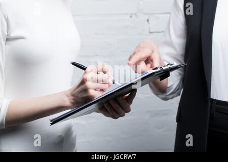 partial view of business people discussing work and making notes - Stock Photo