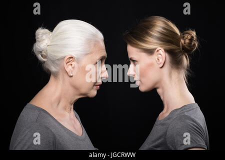 women looking at each other, young and senior people isolated on black - Stock Photo