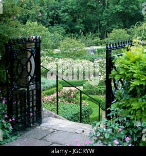 Open black gate in garden - Stock Photo