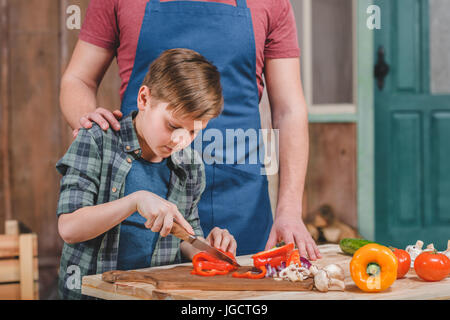 Father in apron helping son cutting fresh vegetables outdoors, dad and son cooking concept - Stock Photo