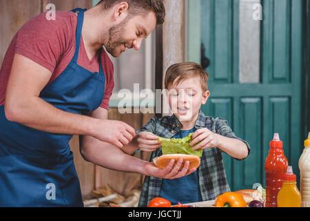 Smiling father and son preparing hot dog together in backyard, dad and son cooking concept