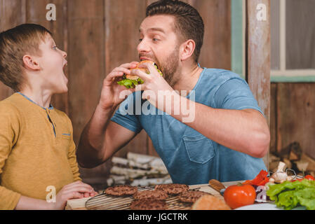 side view of man eating homemade burger with little son near by - Stock Photo