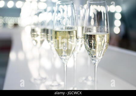 Champagne glasses on white background in bright lights. Fashion show backstage - Stock Photo
