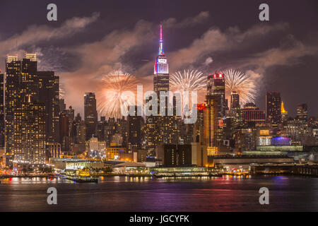 The annual Macy's Fourth of July fireworks show lights the sky behind the Manhattan skyline in New York City as - Stock Photo