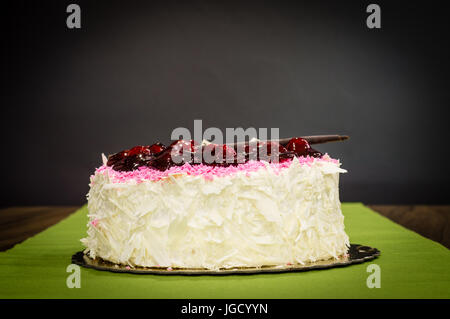 Delicious creamy whole white chocolate cake with cherries on top on a dark background - Stock Photo