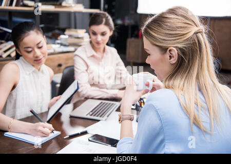 blonde businesswoman drinking coffee while her colleagues working near in modern office