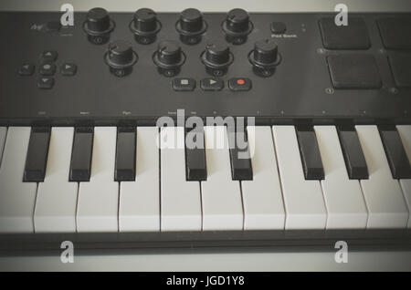 Woman hand playing Piano or electone midi keyboard, electronic musical synthesizer white and black key. - Stock Photo
