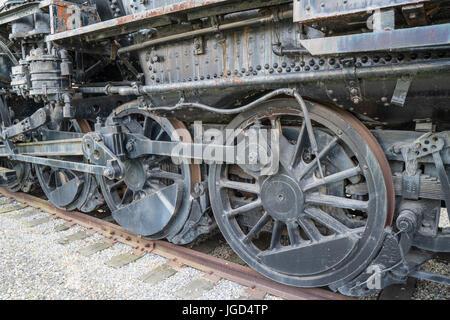 Rusty steel & iron locomotive drive wheels of a steam train. - Stock Photo
