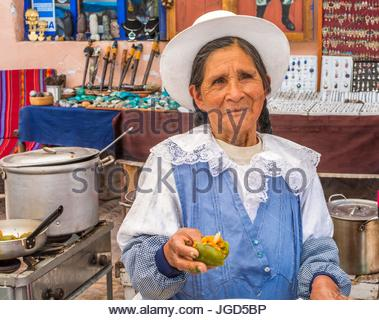 Peru woman wearing a hat prepares food at the Sunday Market in Pisac, Peru, South America. - Stock Photo