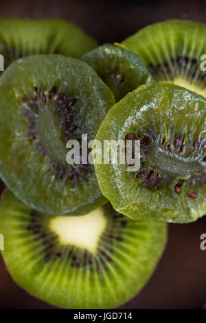 Macro detail of dried kiwi slices with ripe fruit halves on wooden background - Stock Photo
