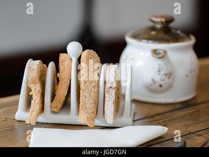Four slices of toasted bread in toasts holder on wooden table close up. Foreground focus, tea pot in blurred background. - Stock Photo
