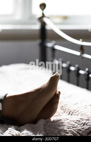 Young adult women, in her fourtys, lying down on vintage style bed at bright window. Focus on feet. Vertical crop, - Stock Photo