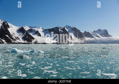 The still, clear water of a bay at the tongue of a glacier is speckled with floating fragments of ice from a recent - Stock Photo
