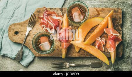 Flatlay of rose wine, prosciutto ham, melon, top view - Stock Photo