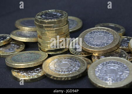 A pile of British sterling coins - new pound coins and two-pound coins against a dark background - Stock Photo