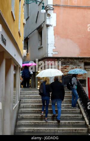 Pedestrians crossing over a canal via a small bridge in the rain, Venice,Venzia, Italy - Stock Photo