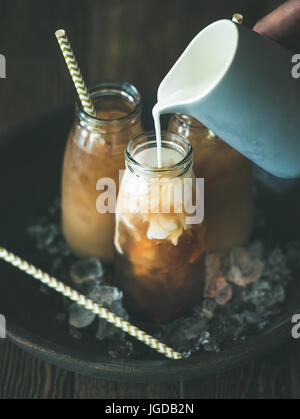 Cold Thai iced tea drink in glass bottles with milk - Stock Photo