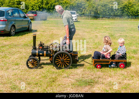 Man driving his miniature replica scale model traction engines with his two children in a trailer at a steam rally - Stock Photo