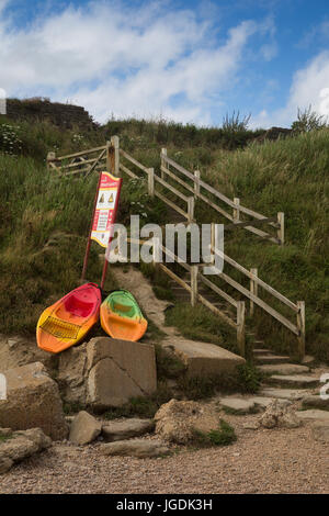 Colourful boats and crooked stone steps with wooden handrails on Jurrasic coast leading down to Eype beach, Symmondsbury, - Stock Photo