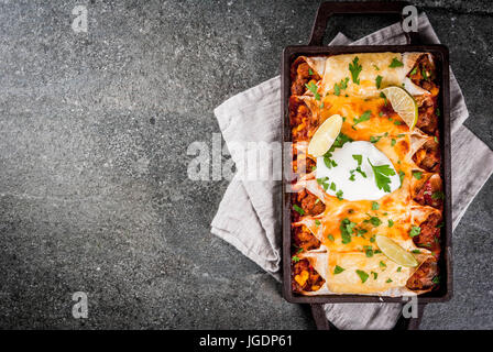 Mexican food. Cuisine of South America. Traditional dish of spicy beef enchiladas with corn, beans, tomato. On a - Stock Photo