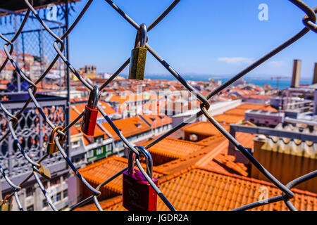 Locks as a proof of love attached to a fence over the rooftops of Lisbon - LISBON - PORTUGAL 2017 - Stock Photo