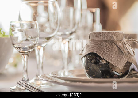 Rustic table setting for a wedding celebration in nice cozy restaurant. Wineglasses, plates and food on table. Guests - Stock Photo