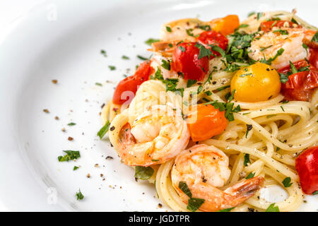 Seafood. Spaghetti pasta with prawns or shrimps with mixed colours cherry tomatoes fresh parsley and pepper. - Stock Photo