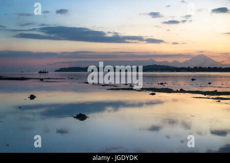 Boat in the ocean with view to Gili Meno from Gili Air during sunset, Lombok, Indonesia - Stock Photo
