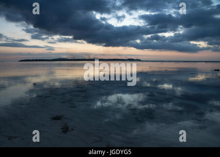 View to Gili Meno from Gili Air during sunset with volcano of Bali and cloudscape in the background, Lombok, Indonesia - Stock Photo