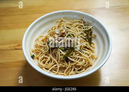 Bowl of Chinese noodle for lunch on the wooden table. - Stock Photo