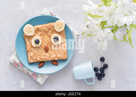 Breakfast / snack / school lunch for kids: peanut butter toast with banana, blueberry and almonds shaped as funny - Stock Photo